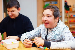 Lyckliga ungar med handikapp framkallar deras fina motoriska expertis på rehabiliteringmitten för ungar med speciala behov Royaltyfri Bild
