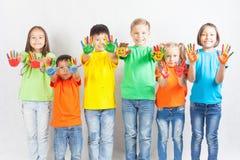 Lyckliga ungar med målat le för händer arkivfoto