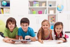 Lyckliga ungar med minnestavladatorer Royaltyfria Bilder