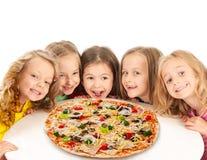 Lyckliga ungar med stor pizza Arkivfoto