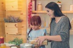 Lyckliga ungar med systern lagar mat sunt mål i köket, Royaltyfri Foto