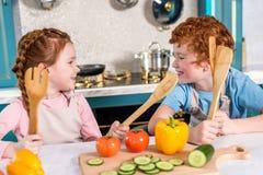 lyckliga ungar med träredskap som ler sig, medan laga mat tillsammans royaltyfria foton
