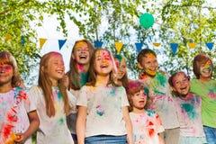 Lyckliga ungar målade i färgerna av den Holi festivalen Arkivbild