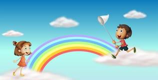 Lyckliga ungar nära den färgrika regnbågen Arkivbild