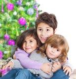 Lyckliga ungar near julgranen Royaltyfri Fotografi