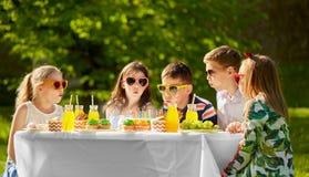 Lyckliga ungar på födelsedagpartiet på sommar arbeta i trädgården royaltyfri foto