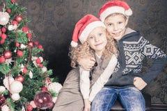Lyckliga ungar på jul semestrar nära dekorerat julträd fotografering för bildbyråer