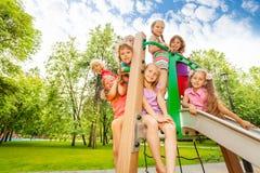 Lyckliga ungar på lekplats chute i parkera Arkivfoton