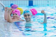 Lyckliga ungar på simbassängen Unga och lyckade simmare poserar arkivbild