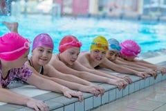 Lyckliga ungar på simbassängen Unga och lyckade simmare poserar royaltyfria foton