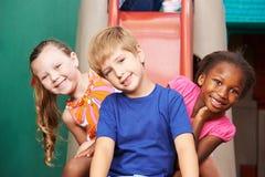 Lyckliga ungar på glidbana i dagis Arkivfoto
