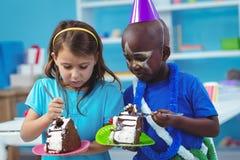 Lyckliga ungar som äter födelsedagkakan Arkivbild