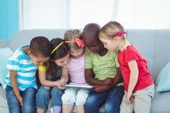 Lyckliga ungar som använder teknologi, medan sitta arkivbild