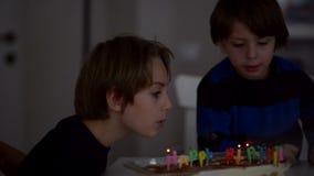 Lyckliga ungar som blåser stearinljus på årsdagen stock video