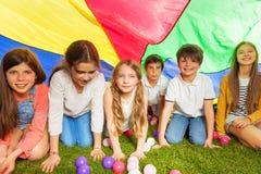 Lyckliga ungar som döljer under färgrikt, hoppa fallskärm utomhus- Royaltyfria Foton