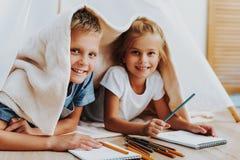 Lyckliga ungar som drar tillsammans att täcka vid filten royaltyfria foton