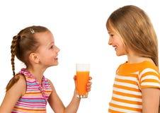 Lyckliga ungar som dricker fruktsaft Arkivbilder