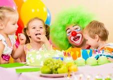 Lyckliga ungar som firar födelsedagdeltagaren med clownen Arkivfoton