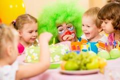 Lyckliga ungar som firar födelsedagdeltagaren med clownen Royaltyfria Bilder