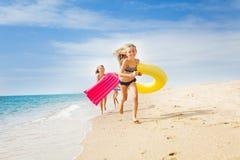 Lyckliga ungar som har ett lopp på den soliga stranden i sommar royaltyfri bild