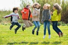 Lyckliga ungar som har gyckel och hoppar upp Royaltyfria Bilder