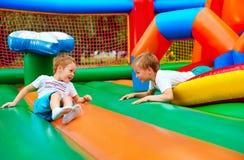 Lyckliga ungar som har gyckel på uppblåsbar dragningslekplats Fotografering för Bildbyråer