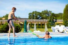 Lyckliga ungar som har gyckel som spelar i vatten, parkerar Fotografering för Bildbyråer
