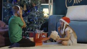 Lyckliga ungar som hemma packar upp julgåvor lager videofilmer