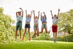 Lyckliga ungar som hoppar och har gyckel i sommar, parkerar Arkivfoto