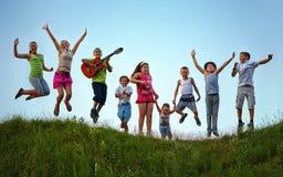 Lyckliga ungar som hoppar på sommarfält Arkivfoton
