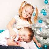 Lyckliga ungar som kelar nära julgranen Arkivbild