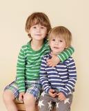 Lyckliga ungar som kramar och ler Arkivbild