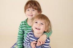 Lyckliga ungar som kramar och ler Arkivfoton