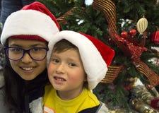 Lyckliga ungar som lägger under julträdet Arkivbild