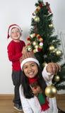 Lyckliga ungar som lägger under julträdet Arkivbilder
