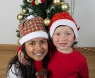 Lyckliga ungar som lägger under julträdet Royaltyfri Foto