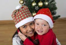 Lyckliga ungar som lägger under julträdet Fotografering för Bildbyråer