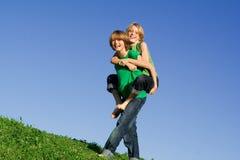 lyckliga ungar som leker på ryggen Fotografering för Bildbyråer