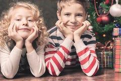 Lyckliga ungar som ligger på golvet under julgranen Royaltyfria Bilder