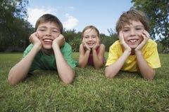 Lyckliga ungar som ligger på gräs arkivbilder