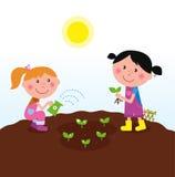 lyckliga ungar som planterar växter två som bevattnar Arkivbild