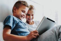 Lyckliga ungar som sitter med den digitala minnestavlan på säng arkivfoton