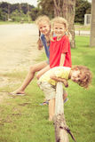Lyckliga ungar som sitter på gräset Arkivbilder
