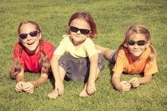 Lyckliga ungar som sitter på gräset Fotografering för Bildbyråer