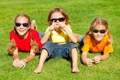 Lyckliga ungar som sitter på gräset Royaltyfria Foton