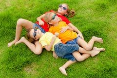 Lyckliga ungar som sitter på gräset Royaltyfri Foto