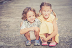 Lyckliga ungar som sitter på vägen Arkivfoton