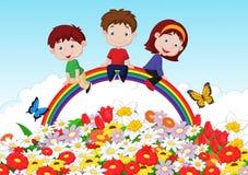 Lyckliga ungar som sitter på regnbågen över blommabakgrund Arkivbild