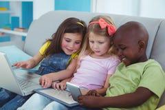 Lyckliga ungar som sitter samman med en minnestavla och en bärbar dator och en telefon Arkivfoton
