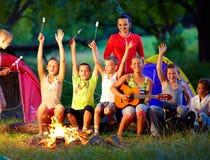 Lyckliga ungar som sjunger sånger runt om lägerbrand Arkivbild